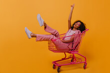 Enthusiastic Brunette Girl Expressing Sincere Positive Emotions. Studio Shot Of Beautiful Woman Sitting In Shopping Cart.
