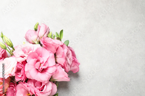 Fotografering Beautiful bouquet of pink Eustoma flowers on light grey background, top view