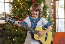 Smiling 4 Year Old Boy Playing Guitar With Christmas Tree In Background