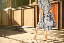 Woman In Stylish Light Blue Polka Dot Dress And High Heel Shoes With Handbag On City Street, Closeup