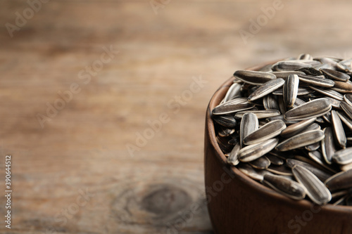 Raw sunflower seeds on wooden table, closeup. Space for text Fototapet