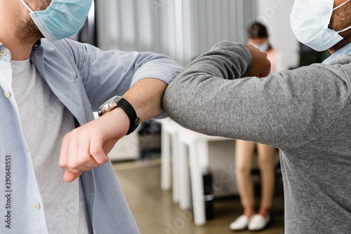 Obraz Cropped view of multiethnic businessmen in medical masks giving high five with elbows in office - fototapety do salonu