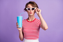 Photo Of Charming Lady Hold Specs Soda Plastic Takeaway Cup Send Air Kiss Wear Sunglass Striped T-shirt Isolated Purple Color Background