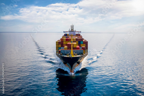 Obraz na plátně Aerial front view of a loaded container cargo vessel traveling over calm ocean