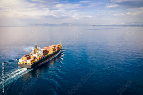 Aerial view of a loaded cargo container ship traveling over calm ocean towards t Canvas Print