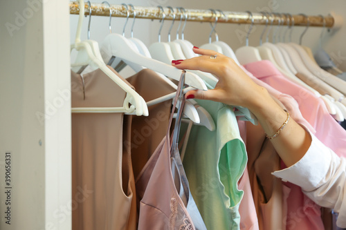 Photo woman's hand pulls a hanger with a nightgown from the closet