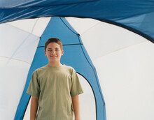 Happy Adolescent Boy Standing Upright In A Dome Camping Tent