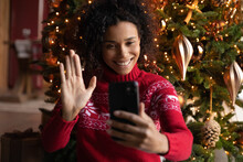 Close Up Smiling African American Woman Using Phone, Looking At Screen, Waving Hand, Greeting, Chatting Online With Friends Or Relatives, Making Video Call On Christmas Tree Background At Home