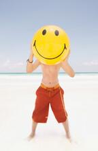 Young Boy Holding A Smiley Face Beach Ball Over His Face