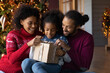 Close up happy African American family unpacking Christmas gift, smiling mother and father with adorable little daughter unwrapping present box, sitting near festive tree at home, winter holiday