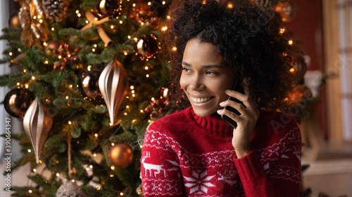 Obraz Close up smiling African American young woman talking on phone, sitting near festive Christmas tree at home, happy female holding smartphone, chatting with friends or relatives, congratulating - fototapety do salonu
