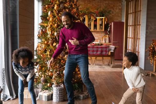 Slika na platnu Overjoyed African American father with adorable kids having fun on winter holida