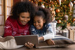 Close up happy African American woman with daughter using tablet together, lying on soft pillows near Christmas tree at home, happy family shopping online, choosing gifts, enjoying winter holiday