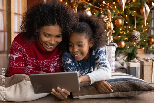 Obraz Close up happy African American woman with daughter using tablet together, lying on soft pillows near Christmas tree at home, happy family shopping online, choosing gifts, enjoying winter holiday - fototapety do salonu