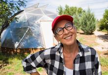 Senior Woman Gardening In Geodesic Dome,Santa Fe,NM.