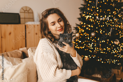 Fototapeta Happy girl in knitted cozy clothes hugs her cat sitting on the sofa near the decorated Christmas tree in the bright interior of the house