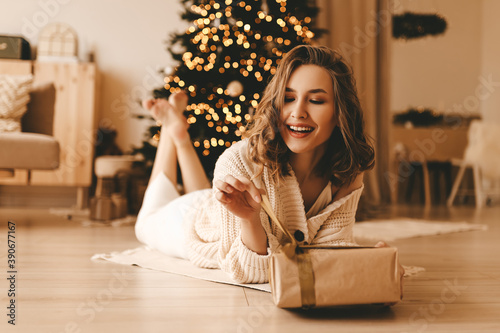 Happy emotional surprised young woman opens a holiday gift sitting on the floor Fototapet