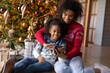 Leinwandbild Motiv Happy African American woman with adorable little daughter using phone, looking on smartphone screen, shopping online, choosing gifts, sitting on warm floor near Christmas tree at home