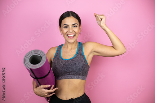 Young beautiful woman wearing sportswear over isolated pink background showing arms muscles smiling proud Billede på lærred