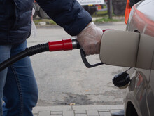 A Man Refuels A Car With A Disposable Glove. Safety From Germs.prevention From Coronavirus