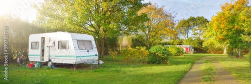 Caravan trailer with a bicycle parked on a green lawn under the trees in a camping site Fotobehang