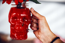 Creative Halloween Day Composition. Red Flowers In The Skull Glass Mug. Drink For Night Party. Woman Holding Drink.