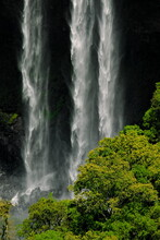 Three Large Streams Of White Water, Falling Hard On The Black Stones Among The Vegetation, In The Caracol Waterfall.