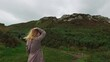 The girl in long coat walks down the hill. View of a young woman from the back. Tracking in Ireland near Dublin. High quality FullHD footage video.