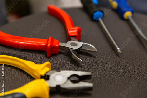 Photo Laying a wire pair of pliers and screwdrivers locksmith work tool close-up on a