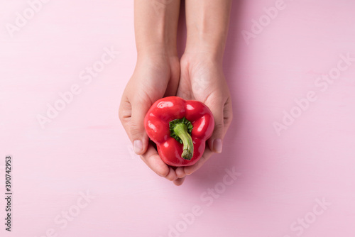 Fotografia Red bell pepper holding by hand on pink background, Top view