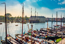 Stunning Shot Of Many Moored Sailboats With Amsterdam Modern Traditional Buildings In The Background