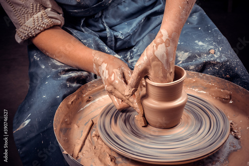 Fotografia, Obraz Craftsman siting on bench with pottery wheel and making clay pot