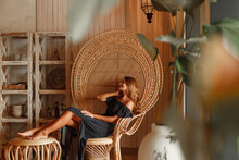 Young Woman  In Black Long Dres Dress Is Sitting In Vintage Wicker Chair And Smiling Cute In Boho Style Interior Background