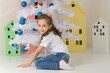 Preteen Girl Posing in Front of White Christmas Tree with Blue Baubles.