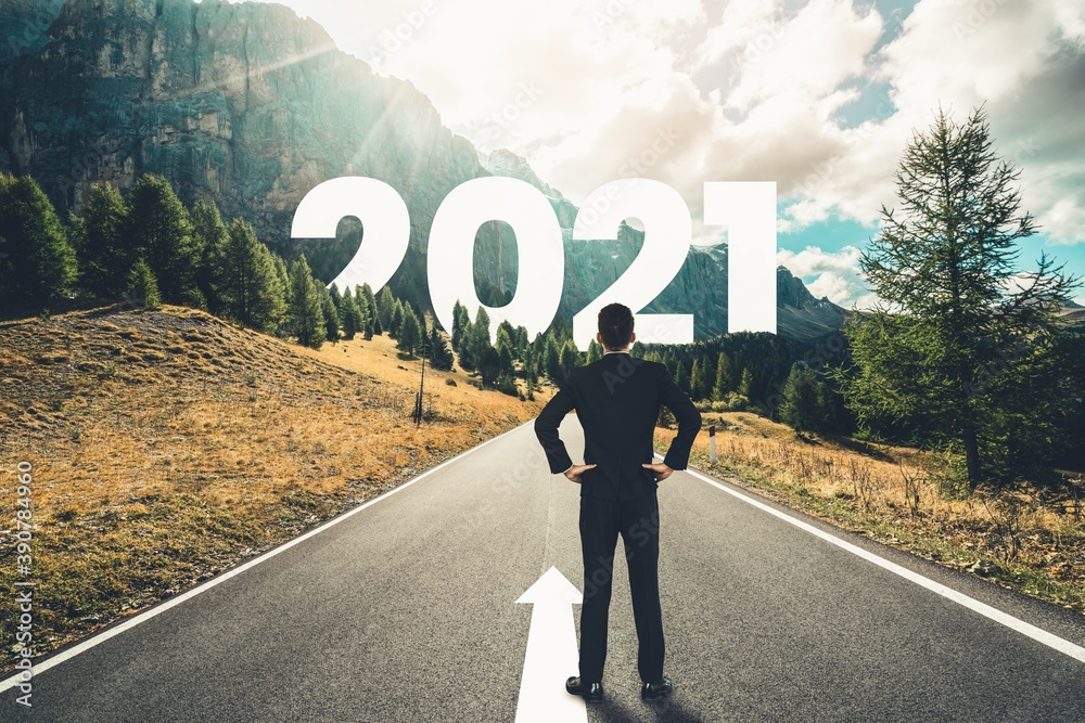 Fototapeta The 2021 New Year journey and future vision concept . Businessman traveling on highway road leading forward to happy new year celebration in beginning of 2021 for fresh and successful start .
