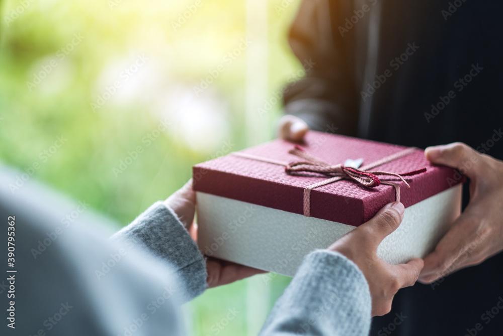 Fototapeta Closeup image of a man giving a woman a gift box