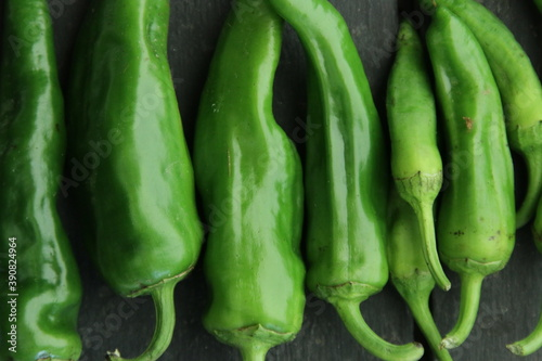 Green chili peppers on a vintage table Fotobehang