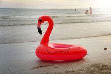 A Red Flamingo Shaped Rubber Ring On The Beach By The Sea.