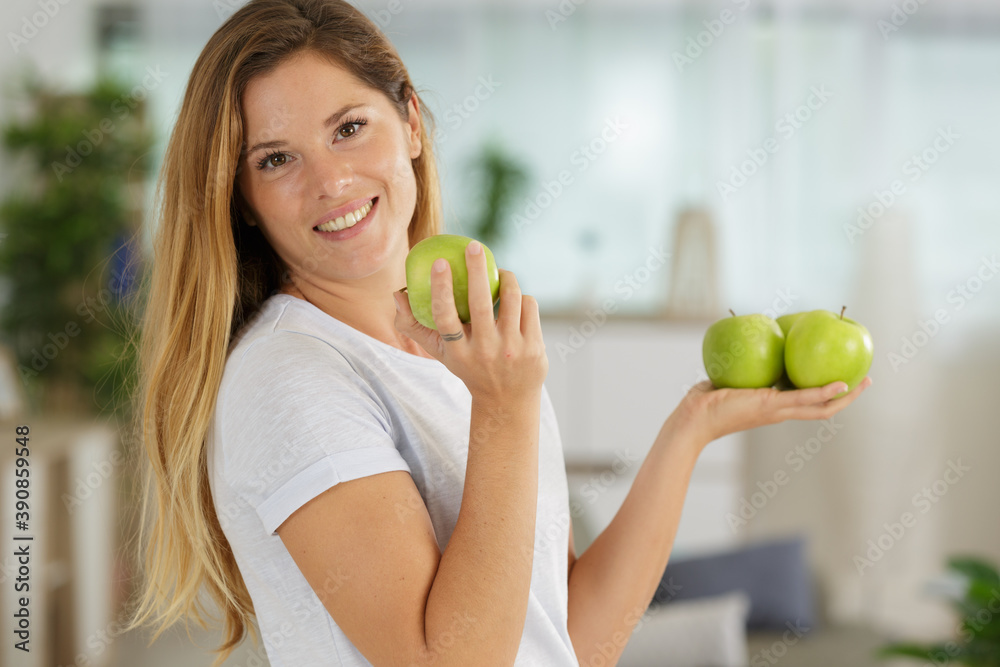 Fototapeta happy woman biting a green apples