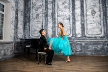 A Young Man Sits At The Piano And Looks At A Dancing Partner Standing Next To Him