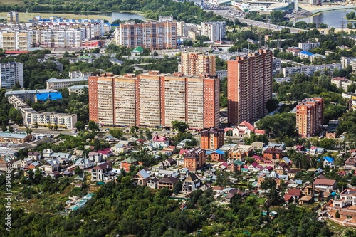 Aerial veiw of Ulyanovsk cityscape: huge blocks of flats built from red brick and district of  detached houses in front of them Fotobehang