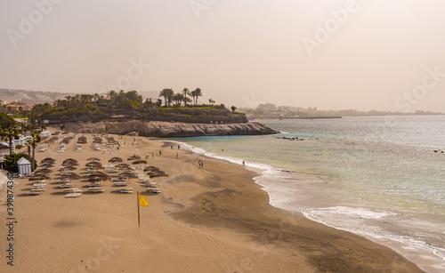 Fotografie, Obraz Empty sun loungers on beach on windy misty day at Costa Adeje, Teneriffe, Spain