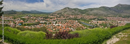 Cuadros en Lienzo The panoramic view on plenty of tile roof houses in the lowland in summer and mountains in the background in Bosnia and Herzegovina