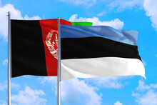 Estonia And Afghanistan National Flag Waving In The Wind On A Deep Blue Sky Together. High Quality Fabric. International Relations Concept.
