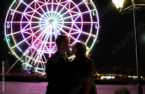 young man and woman romance love in the night in amusement park near ferris whee Fotobehang