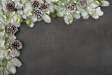 Winter Snow Covered Spruce Fir Background Border With Pine Cones & Mistletoe On Grey Grunge. Frame Design  For The Solstice, Christmas & New Year Festive Season. Top View, Flat Lay, Copy Space.