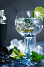 Glass Of Gin And Tonic With Mint, Lime Wedges, Blueberries And Ice On A Grey Background