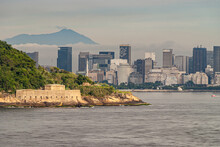 Rio De Janeiro, Brazil - December 22, 2008: Yellow Stone Sao Joao Fortification At Entrance To Gray Water Guanabara Bay With Office Towers Skyline Of Gloria District Under Gray Sky.