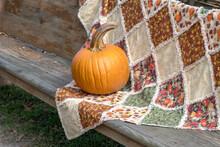 Round Orange Pumpkin On A Handmade Fall Quilt