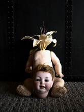 Creepy Doll With A Flower For A Head And The Head Between The Legs On The Ground